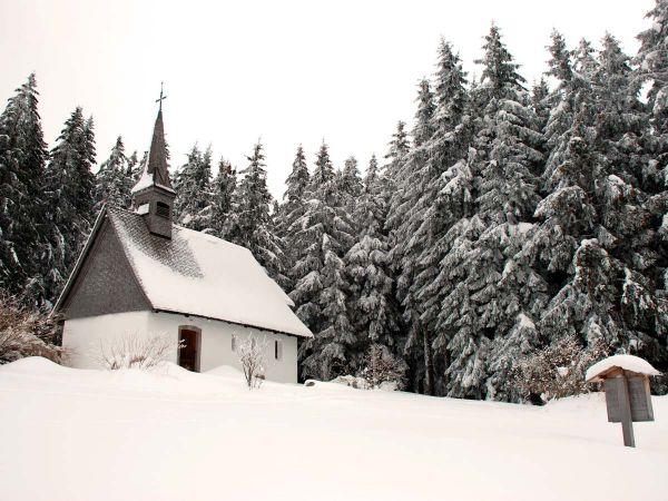 Schnee bedeckt die Martinskapelle und den Schwarzwald